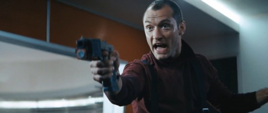 Jude Law pointing a gun and looking screaming mad.