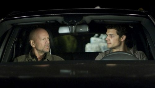 Bruce Willis and Henry Cavill stare warily at each other.
