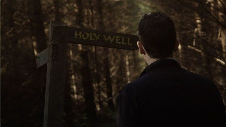 Ger looks at the Holy Well signpost. Hint: There's nothing holy here.